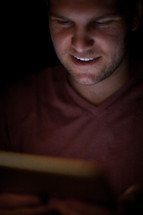 A man illuminated by the light of an electronic tablet.