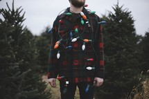a man in a plaid shirt with Christmas lights standing in a Christmas tree lot