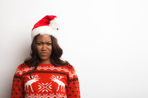 woman in an ugly Christmas sweater and santa hat with a frown
