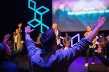 a man with raised hands at a worship service praising God