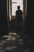 man standing in a window and torn books and pages on the floor