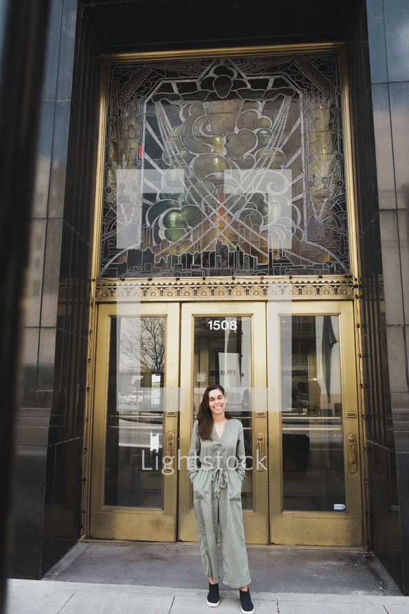 a woman standing in front of a downtown building