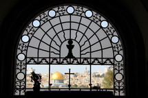 Ornate church window overlooking the old city of Jerusalem and the Dome of the Rock