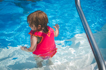 a toddler girl in a life vest in a swimming pool