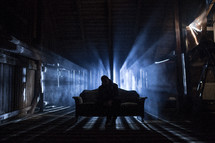 man sitting on a couch in a dark room alone