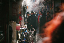 men and motorcycles in a crowded alley