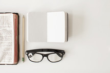 Open Bible with a pencil, journal and reading glasses for taking notes.