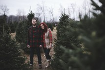 a couple in a Christmas tree lot