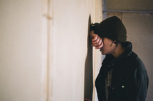 A woman stands with her head against a wall.