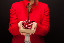 a woman in a red peacoat holding a gift box at Christmas