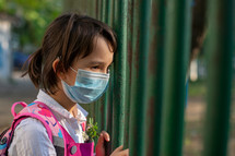 Little school girl going back to school after pandemic outbreak wearing an face mask
