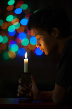 colorful bokeh lights and a boy holding a candle