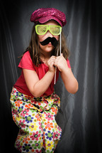 girl child acting silly with sunglasses and a mustache