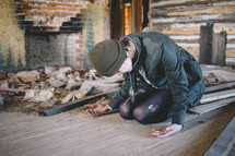 A woman kneels on the floor in prayer in an abandoned house.
