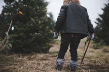 a boy child holding a saw in a Christmas tree lot