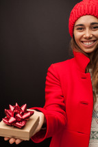 a woman in a red trench coat holding a gift box