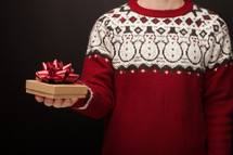 a man in a Christmas sweater holding a gift box