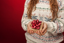 a woman in a sweater holding a gift box