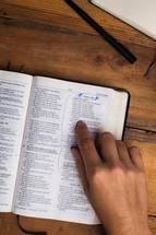 man reading a Bible and pointing to scripture