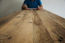 man reading a Bible at the end of a table
