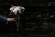 arm of a woman holding out a bouquet of flowers