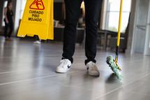 a man holding a dust mop and wet floor sign in a lobby