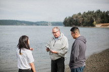 a pastor praying with a family before a baptism in a river outdoors