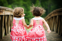 sisters holding hands in matching dresses