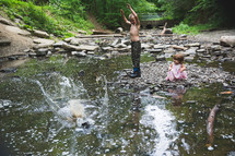 brother and sister playing in a stream
