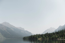 mountain peaks under a foggy sky and lake