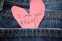 I love you daddy note on a pink paper heart in a jeans pocket