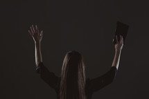 A woman with raised hands in worship to God holding a Bible