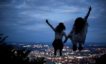 friends jumping up celebrating and view of distant suburbs at night