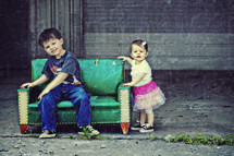 brother and sister sitting on a tiny couch outdoors