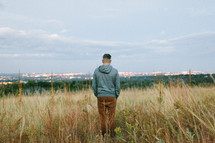 a man standing in a field of tall grasses