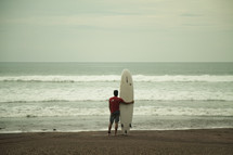 man on a beach with a surfboard