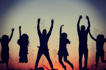 silhouettes of young adults jumping outdoors at sunset