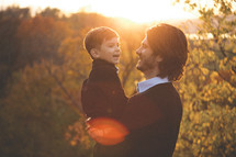 father holding his son outdoors under sunlight