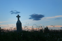 cross on a tombstone at sunset