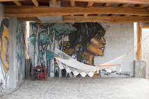 hammock and generator in front of a mural on a wall