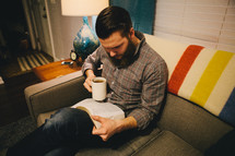 A man reading a Bible while sitting on a couch.