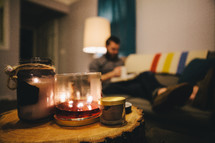 A burning candle and a man reading a Bible on a couch in the distance.
