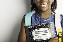 a smiling girl with missing teeth holding a composition notebook
