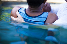 Man being baptized in a pool of water.