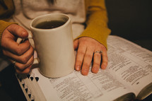 A woman holding a coffee cup and reading a Bible.