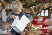 A child opening a Christmas present Christmas morning.