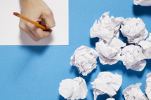 paper balls and a person writing