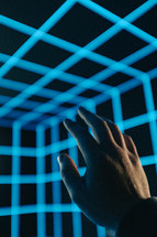 hand reaching up in 3D light cube
