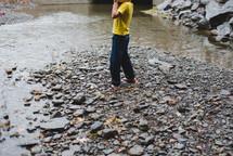 a barefoot boy skipping rocks in a stream