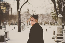 grieving woman in black in a snow covered cemetery